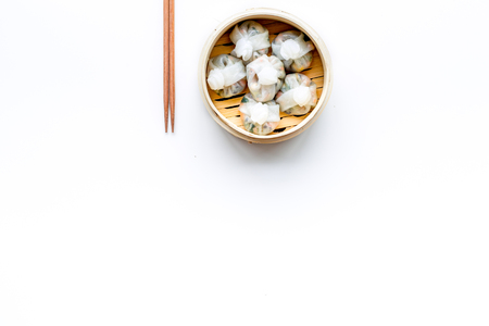 Dim sums with red pepper and vegetables with sticks in Chinese restaurant on white background top view mockup