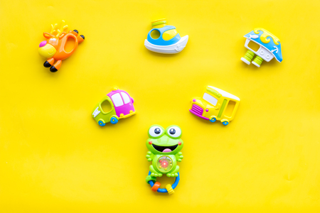Craft toys for kids. Developing rattle for the smallest and baby bottle with milk. Yellow background top view mock up Фото со стока