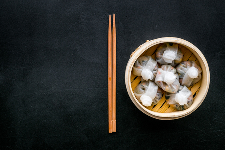 Dinner in Chinese restaurant with dim sum, sticks on black table background top view space for text