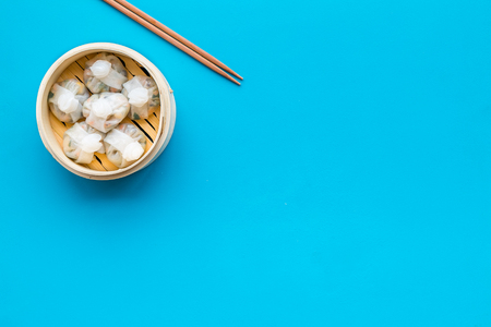 Chinese food set with dim sum, sticks on blue background top view copy space