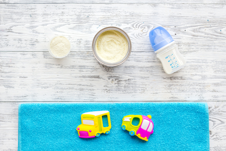 Craft toys for kids. Developing rattle for the smallest and baby bottle with milk. White wooden background top view