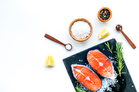 Fresh salmon steak with spices, rosemary, lemon for cooking healthy food on white background top view mock-up