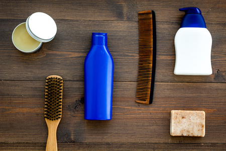 Male care set for barbershop with shampoo bottle and comb on wooden background top view mock-up