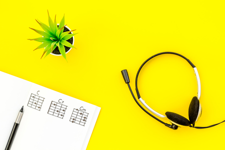 songwriter or dj work place with notes and headphones on yellow background top view Stock Photo