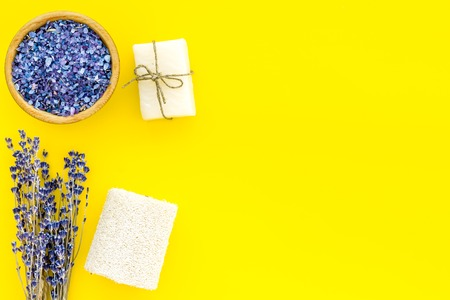 Spa set with lavender spa salt. Purple spa salt near dry lavender branches and washcloth on yellow background top view space for text