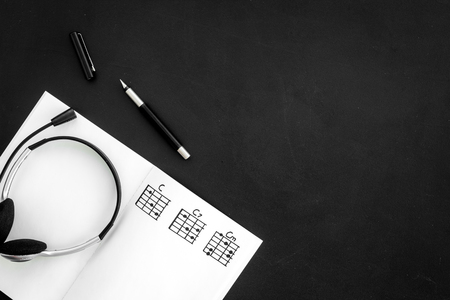 musician work set with notes and headphones black table background top view copy space
