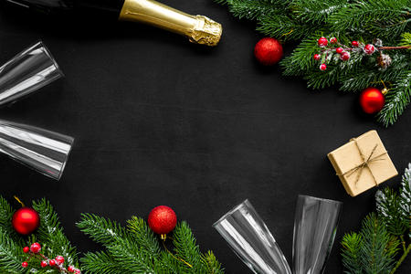 New Year celebration with spruce branch, champagne and glasses black table background top view mock up Stock Photo