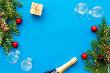 New Year celebration with spruce branch, champagne and glasses blue table background top view mock up