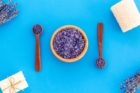 Spa set with lavender spa salt. Purple spa salt near dry lavender branches and washcloth on blue background top view pattern Stock Photo