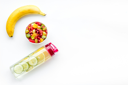 Weight loss concept. Fruit salad near fruit lemon and cucumber water on white background top view copy space