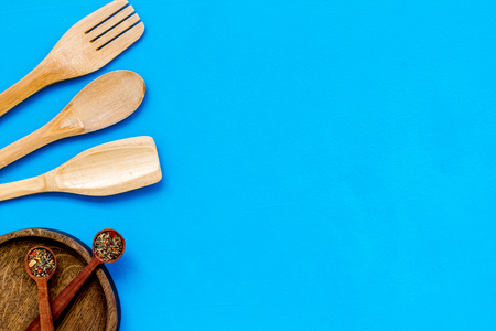 Village wooden cutlery set on blue background top view mock-up