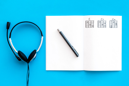 musician work set with notes and headphones blue table background top view copy space