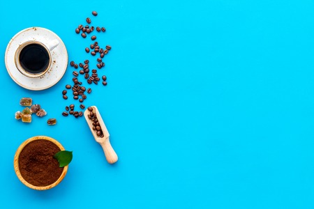 Brown roasted coffee beans scattered on blue background and cup of americano top view mockup
