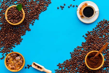 Coffee concept. Roasted beans, ground coffee and cup of espresso on blue background top view copy space Stock Photo