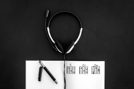 songwriter or dj work place with notes and headphones on black background top view
