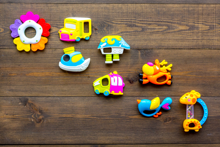 Baby care with craft toys for newborn. Rattle. Wooden background top view copy space Foto de archivo - 114075775