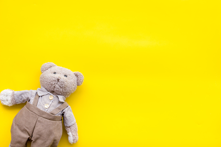 Toys for newborn baby set with teddy bear and clouds on yellow background flat lay space for text