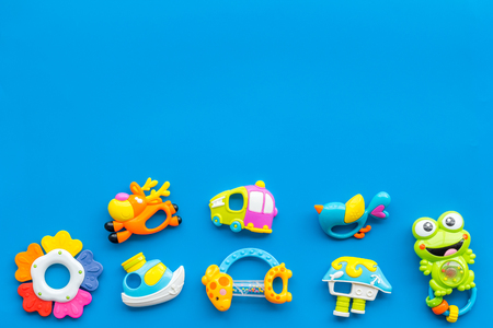 Toys for newborn baby set with plastic rattle on blue background flat lay space for text Foto de archivo - 114075777