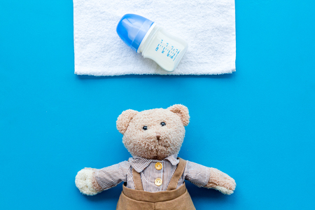 Handmade toys for newborn baby. Teddy bear. Feeding bottle with milk. Blue background top view Stock Photo - 114075779