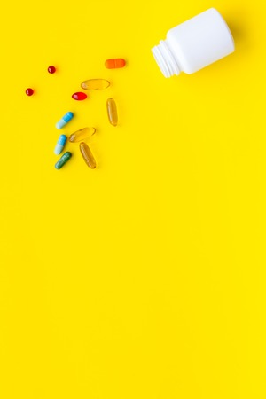 Close up of an open bottle of medicine and its lid. Several pills are lying on yellow desk. Pharmacology and medical supplies. Top view mock-up Banco de Imagens - 114075477