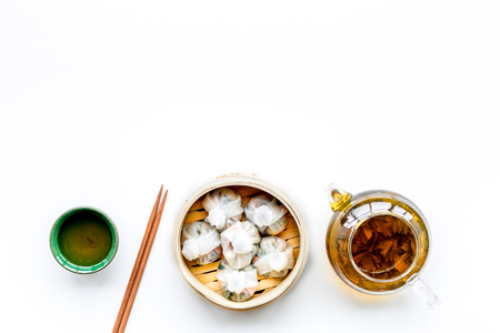 Chinese steamed dumplings Dim Sum in bamboo steamer with tea on white background top view mock up