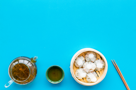 Chinese steamed dumplings Dim Sum in bamboo steamer with tea on blue background top view mock up Stock Photo