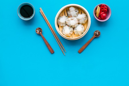 Chinese food set with dim sum, sticks, spices and tea on blue background top view copy space