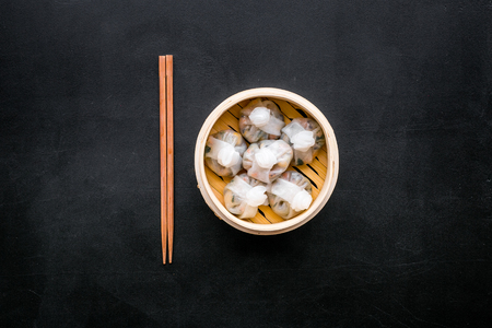 Dinner in Chinese restaurant with dim sum, sticks on black background top view Stock Photo