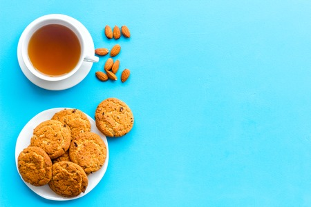 Dessert for evening tea. Cup of tea, fresh homemade cookies on blue background top view space for text