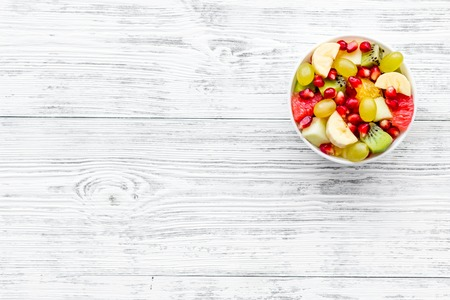 Fruit diet concept. Fruit salad with apple, kiwi and pomegranate in bowl on white wooden background top view space for text Stock Photo