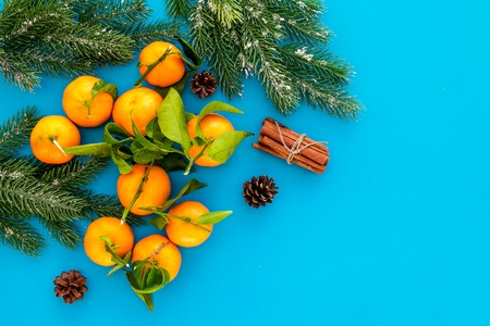 pile of tangerines, fir tree and cinnamon for New Year and Christmas celebration on blue background top view mock up