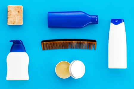 barber workspace with equipment. Shampoo bottle and comb on light blue background top view space for text