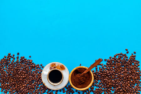Coffee background with beans and cup of Americano blue table flat lay space for text