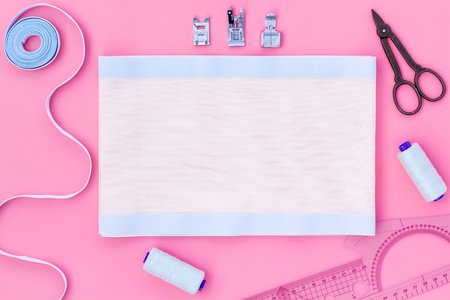 Woman hobby. Set for tailor shop with thread, scissors, fabric on pink background top view copy space Stock Photo