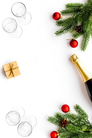 New Year celebration with spruce branch, champagne and glasses white table background top view mock up