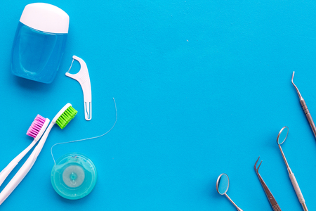 Daily oral hygiene for family. Toothbrush, dental floss and dentist instruments on blue background top view mock up