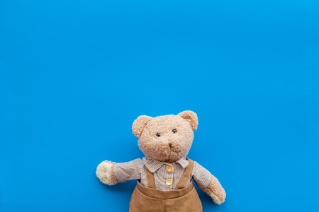 Handmade toys for newborn baby. Teddy bear. Blue background top view mockup Stockfoto