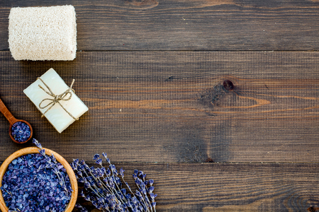 Spa set with lavender spa salt. Purple spa salt near dry lavender branches and washcloth on dark wooden background top view copy space