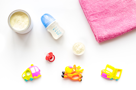 Craft toys for kids. Developing rattle for the smallest and baby bottle with milk. White background top view