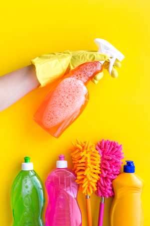 Housekeeping set. Detergents, soap, cleaners and brush for housecleaning on yellow background top view mock-up Stockfoto
