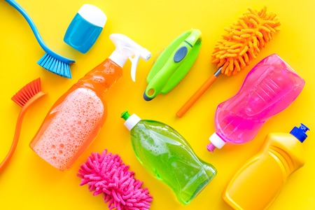 House cleaner tools set with detergents, soap, cleaners and brush on yellow background top view mock up