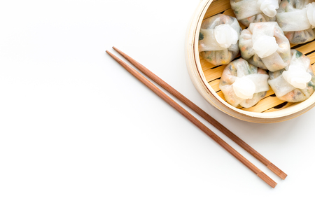 Chinese food set with dim sum, sticks on white background top view copy space