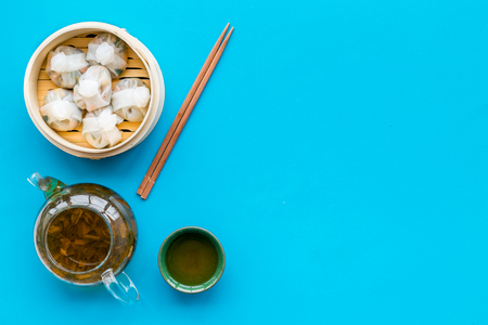 Dim sums with sticks and herbal tea in Chinese restaurant on blue background top view mockup