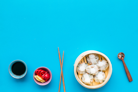 Chinese food set with dim sum, sticks and tea on blue background top view copy space Stock Photo