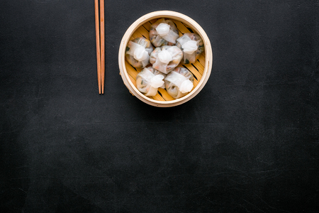 Chinese steamed dumplings Dim Sum in bamboo steamer on black background top view mock up