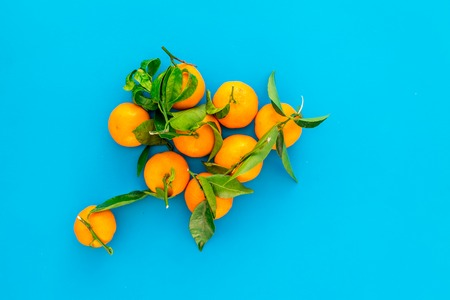 Pile of tangerines for New Year and Christmas celebration on blue background top view