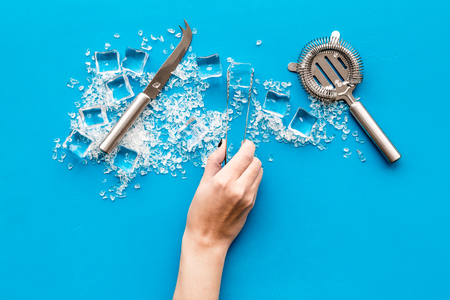Pile of ice cubes and bar equipment on blue bar table top view