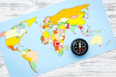 Direzione di viaggio e concetto di pianificazione del viaggio con bussola e mappa del mondo su sfondo di legno grigio vista dall'alto