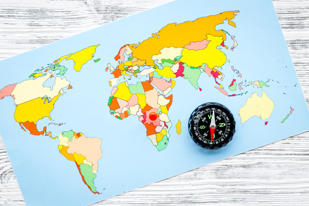 Travel direction and trip planning concept with compass and map of the world on gray wooden background top view