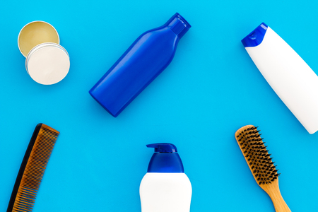 Shampoo bottle and comb for man care in barbershop blue background top view mockup